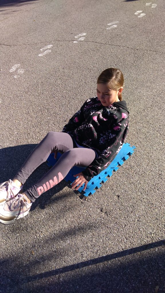 Ecole Sainte Marie Fuveau exercice abdos olympiade 2020 l'enfant assise au sol bras et jambes relevés tient en équilibre le plus longtemps possible