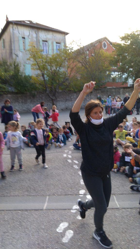 Ecole Sainte Marie Fuveau bras levés enseignante et enfants pour célébrer victoire sportive dans la cour de l'école