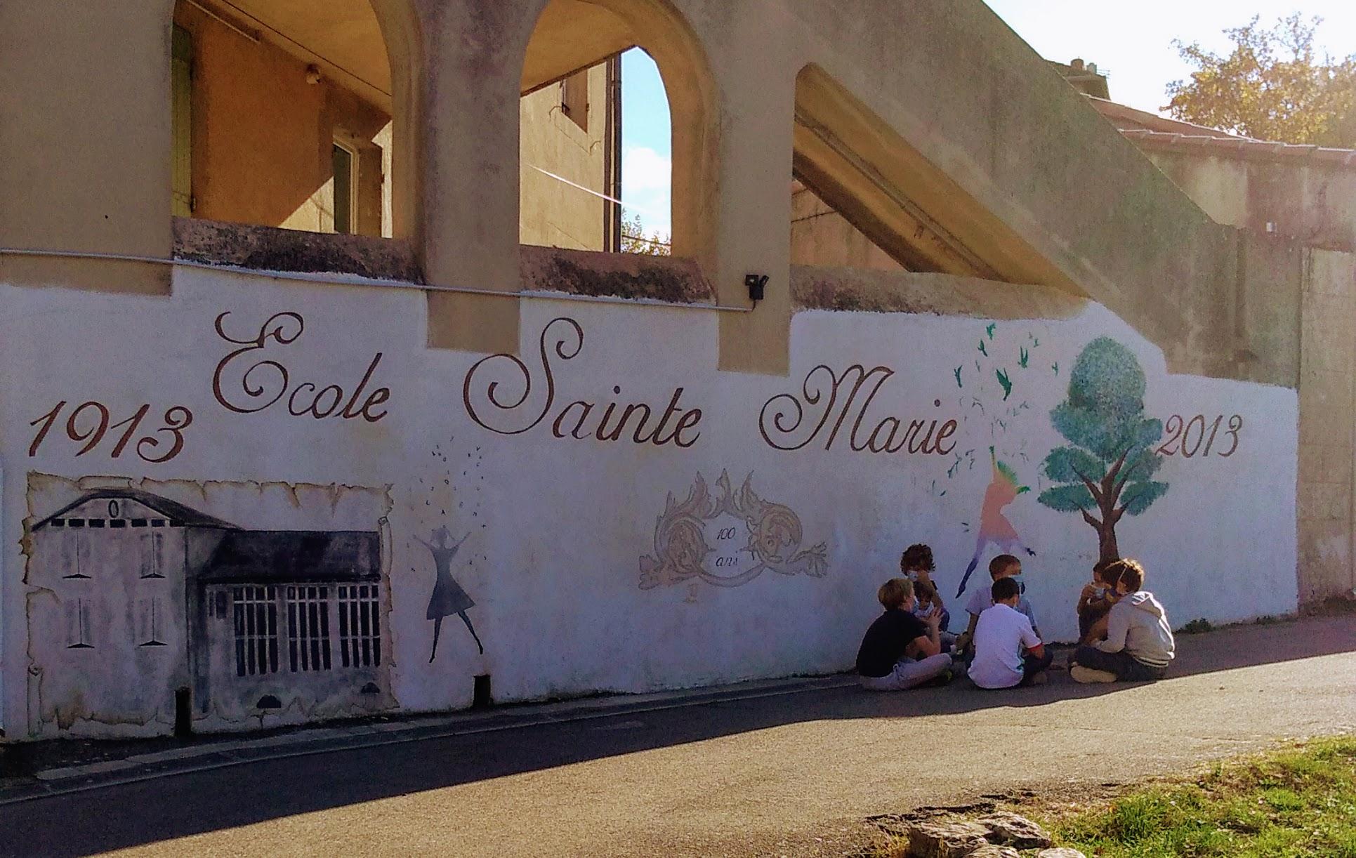Ecole Sainte Marie Fuveau fresque de célébration des cent ans d'existence dessin sur mur de l'école cent ans en arrière noir et blanc et arbre vert avec silouhette enfant très colorée bras en l'air les oiseaux volent au-dessus d'elle