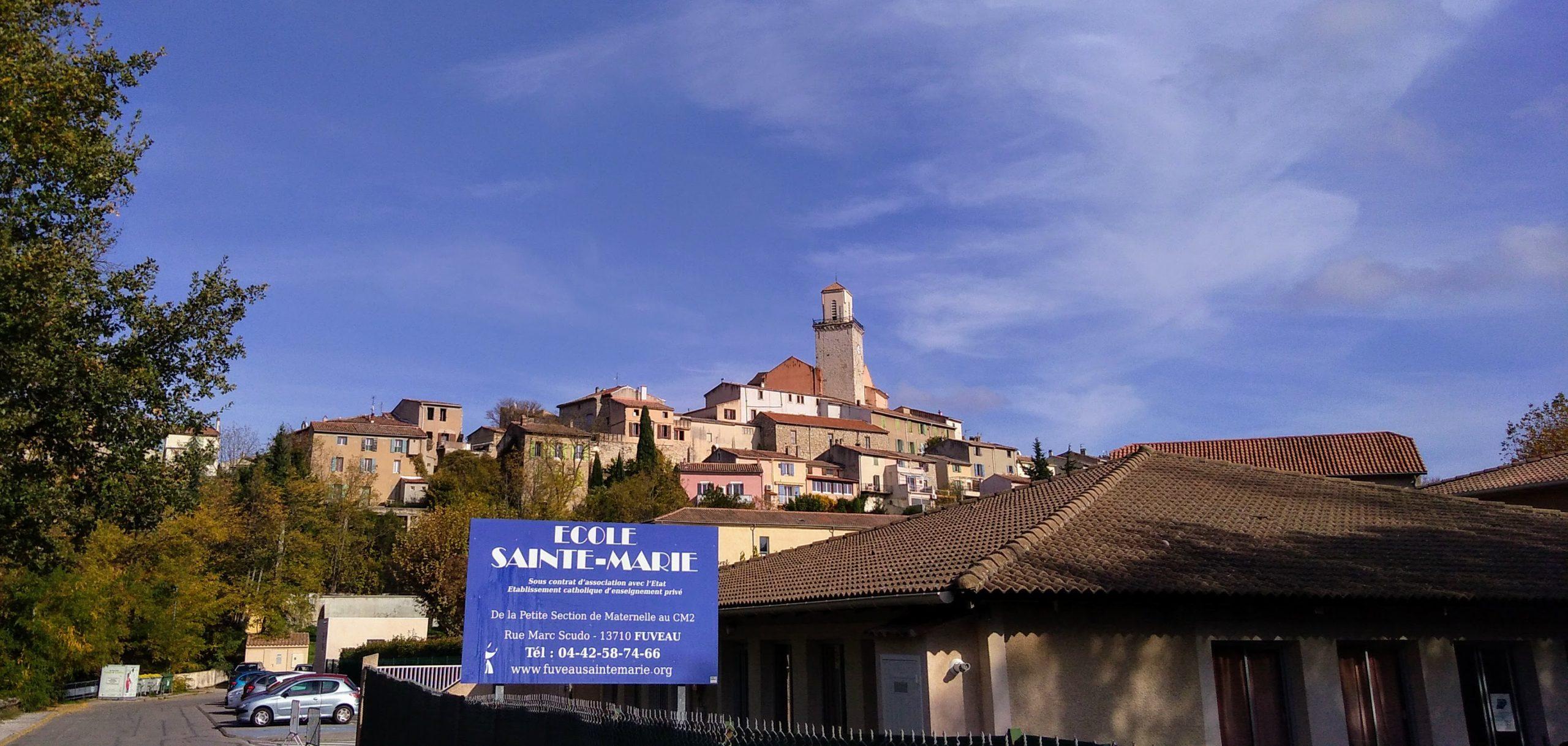 Ecole Sainte Marie Fuveau école engagée photo de l'école le village et son clocher surplombe sur ciel bleu