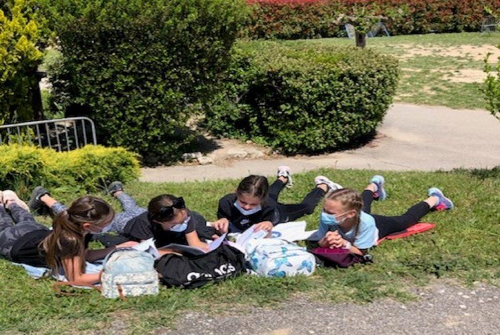 Ecole Sainte Marie Fuveau des enfants lisent dans l'herbe journée rallye lecture