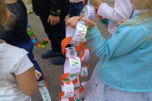 Ecole Sainte Marie Fuveau photo célébration de rentrée scolaire 2021 2022 des enfants tiennent une chaîne confectionnée dans du papier sur chaque maillon est écrit le prénom de tous les enfants de l'école ensemble et unis